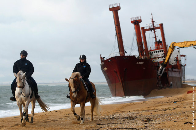Security officers patrol the beach as a crane dismantles the TK Bremen in western France, on January 7, 2012