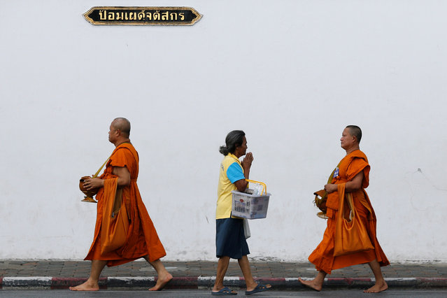 A woman greets Buddhist monks as they arrive for a ceremony at the Grand Palace to commemorate Thailand's King Bhumibol Adulyadej's 70th anniversary on the throne, in Bangkok, Thailand June 9, 2016. (Photo by Jorge Silva/Reuters)
