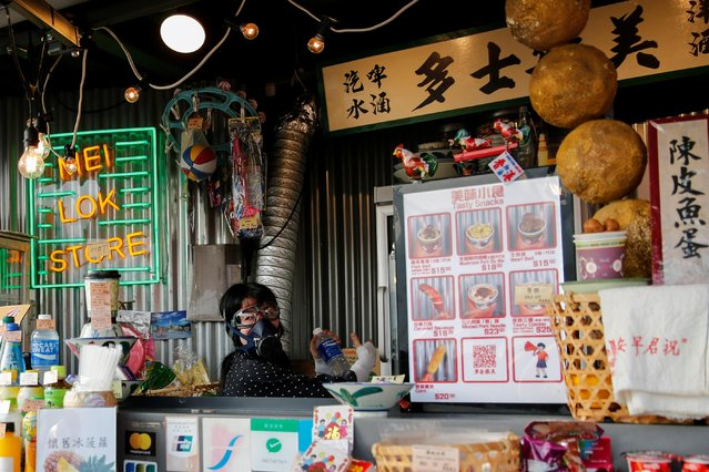 A storekeeper wears gas mask as she sells drinks for protesters while the riot police fire tear gas at Tsim Sha Tsui in Hong Kong, October 27, 2019. (Photo by Tyrone Siu/Reuters)