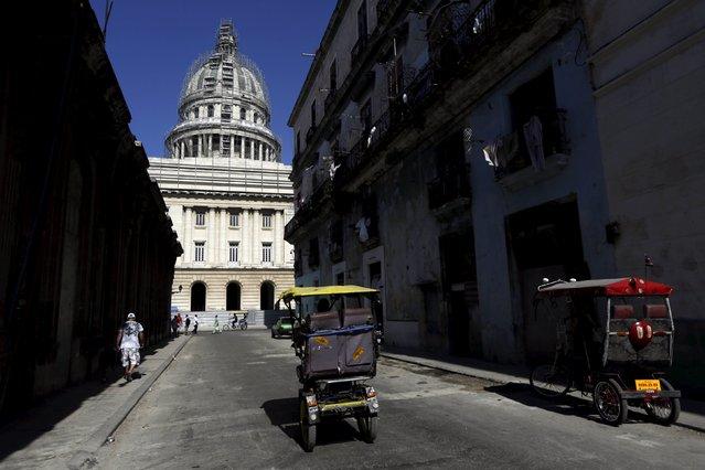 A tricycle taxi passes near Havana's Capitol building April 14, 2015. (Photo by Enrique De La Osa/Reuters)