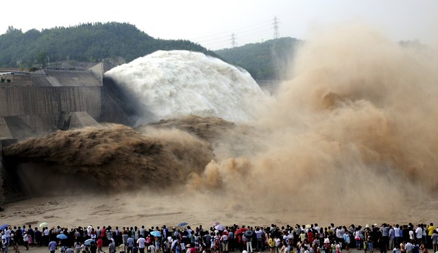 People look on as water gushes from the Xiaolangdi Reservoir section on the Yellow River, during a sand-washing operation in Jiyuan, Henan province July 5, 2014. (Photo by Reuters/Stringer)