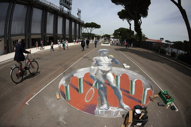 People pass by a painting showing a Roman statue holding a tennis racket on the day of the quarter-finals match of the ATP and WTA Rome tournament on May 18, 2012