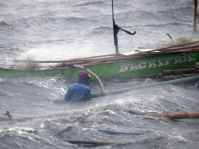 A fisherman secures his boat as Typhoon Rammasun hits the coastal town of Imus, Cavite southwest of Manila. Philippine authorities evacuated almost 150,000 people from their homes and shuttered financial markets, government offices, businesses and schools as typhoon Rammasun gathered strength and hit the capital, Manila. The typhoon, the strongest to hit the country this year, has already torn through eastern islands, toppling trees and power lines and causing blackouts. (Photo by Erik De Castro/Reuters)