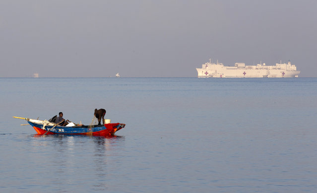 Fishermen work as U.S. Navy's hospital ship USNS Comfort is anchored off Port-au-Prince, Haiti, Friday, November 8, 2019. From Nov. 4 - 13, Haitians will have free access to U.S. military doctors on the ship on a first-come, first-serve basis for general, pediatric, dental, ophthalmological and orthopedic care, at the Killick Coast Guard Base. (Photo by Dieu Nalio Chery/AP Photo)