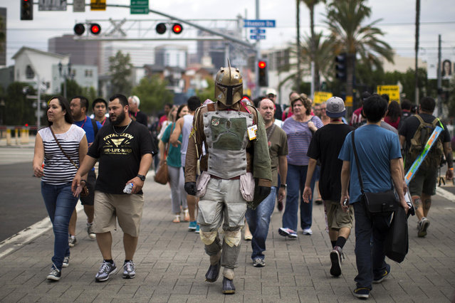 A person wearing a costume to resemble the Star Wars character of Boba Fett crosses the street during the 2014 Comic-Con International Convention in San Diego, California July 25, 2014. (Photo by Mario Anzuoni/Reuters)