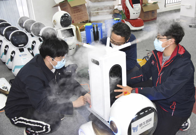 In this photo released by Xinhua News Agency technicians work on a second generation disinfection robot in a technological company in Qingdao, eastern China's Shandong Province on Tuesday, February 11, 2020. Qingdao has called on technological companies to research, develop and refit disinfection robots which can replace human in disinfection operations for possible use in isolation wards of hospitals. (Photo by Li Ziheng/Xinhua via AP Photo)