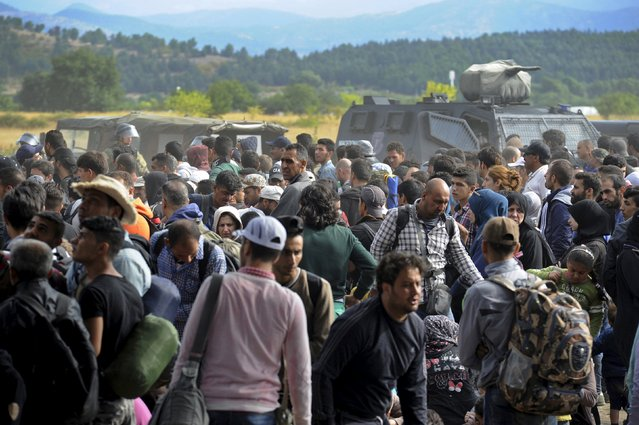 Macedonian police vehicles are seen behind migrants at the Greek-Macedonian border, August 21, 2015. (Photo by Alexandros Avramidis/Reuters)