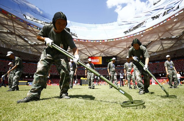 Security personnel sweep the infield with metal detectors after the morning session on the first day of the 15th IAAF World Championships at the National Stadium in Beijing, China August 22, 2015. (Photo by Kai Pfaffenbach/Reuters)
