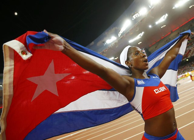 Yarisley Silva of Cuba celebrates with a national flag after winning gold at the women's pole vault final during the 15th IAAF World Championships at the National Stadium in Beijing, China, August 26, 2015. (Photo by Kai Pfaffenbach/Reuters)