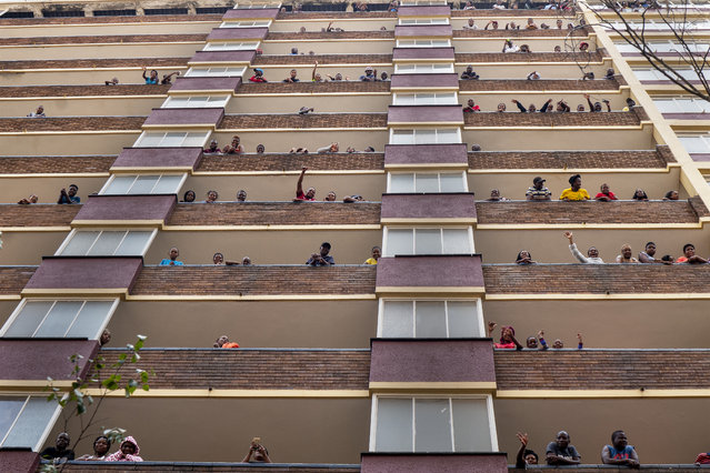 Residents of the densely populated Hillbrow neighborhood of downtown Johannesburg, confined in an attempt to prevent the spread coronavirus, stand and wave from their balconies, Friday, March 27, 2020. (Photo by Jerome Delay/AP Photo)