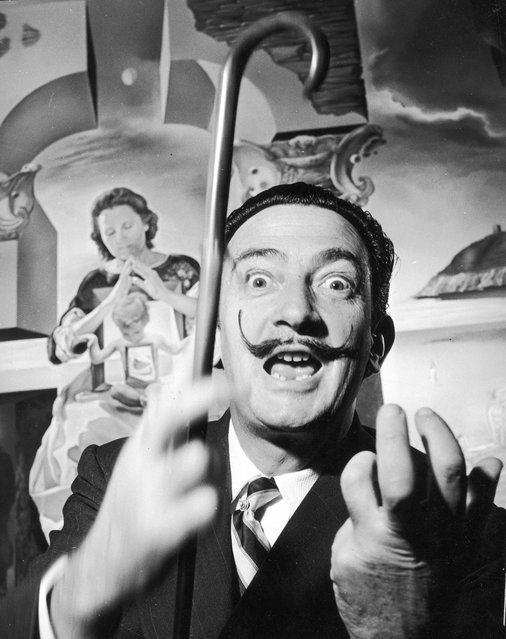 """Spanish surrealist artist Salvador Dali (1904–1989) in London with one of his paintings entitled """"The Madonna of Port Lligat"""", December 1951. (Photo by George Konig/Keystone Features)"""