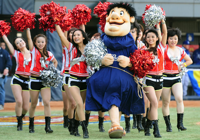 Chinese cheerleaders walk with San Diego Padres mascot the Swinging Friar during entertainment between innings at the first Major League Baseball game in China on March 15, 2008 at the Wukesong Baseball Stadium in Beijing, venue for the 2008 Olympics baseball event. (Photo by Frederic J. Brown/AFP Photo)