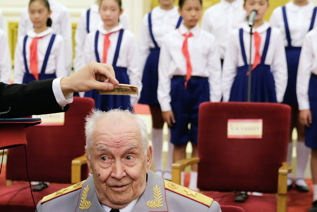 A Chinese officer helps comb the hair of Russian veteran M. A. Gareev after he arrived for a ceremony to honor veterans of World War II and their family members, at the Great Hall of the People in Beijing Wednesday, September 2, 2015. A total of 30 Chinese and foreign war veterans and their family members who made a contribution to victory. (Photo by Andy Wong/AP Photo)