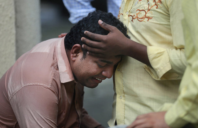 An Indian man mourns outside a morgue for a relative killed in a pedestrian bridge stampede, in Mumbai, India, Friday, September 29, 2017. (Photo by Rafiq Maqbool/AP Photo)