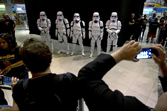 """People dressed as Storm Trooper characters from """"Star Wars"""" await people to purchase toys that went on sale at midnight in advance of the film """"Star Wars: The Force Awakens"""" in Times Square in the Manhattan borough of New York, September 4, 2015. (Photo by Carlo Allegri/Reuters)"""