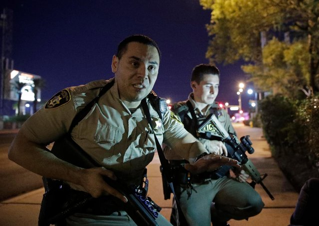 Police officers advise people to take cover near the scene of a shooting near the Mandalay Bay resort and casino on the Las Vegas Strip, Sunday, October 1, 2017, in Las Vegas. (Photo by John Locher/AP Photo)