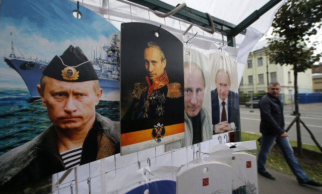 A man walks past cutting boards, that have been painted with images of Russia's President Vladimir Putin, at a street store in the center of St. Petersburg, August 31, 2014. Russia's President Vladimir Putin said on Sunday that Moscow could not stand aside when people were being shot at in Ukraine, he told Russia's state TV Channel 1 in an interview. (Photo by Alexander Demianchuk/Reuters)