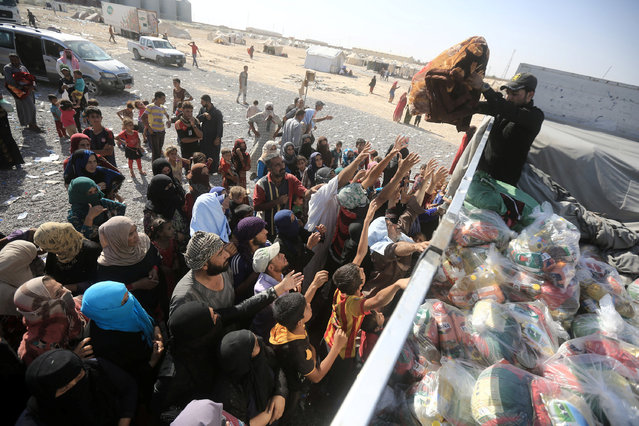 Displaced people, who fled from Al-Shirqat due to Islamic State violence, receive aid on the outskirts of Al-Shirqat, south of Mosul, Iraq, July 30, 2016. (Photo by Reuters/Stringer)