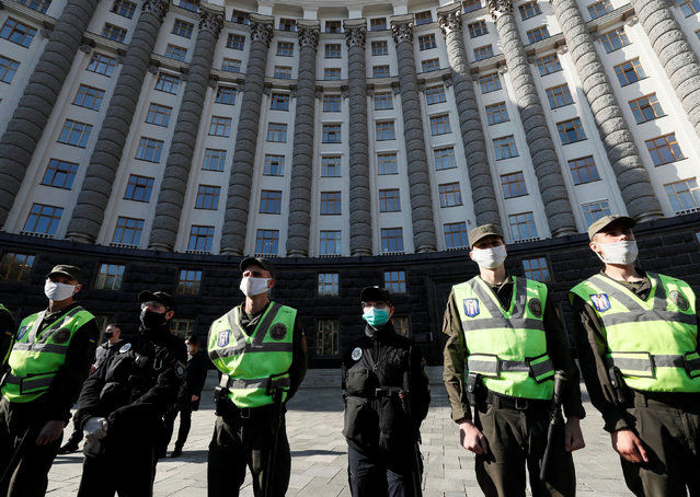 Police officers and members of the National Guard of Ukraine stand guard during a protest to demand support from the government for small businesses and easing of lockdown measures put into place because of the coronavirus disease (COVID-19) outbreak, in front of the Ukrainian cabinet of ministers building in central Kiev, Ukraine on April 29, 2020. (Photo by Gleb Garanich/Reuters)