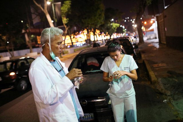 Doctors Carlos Martinez and Maria Martinez eat a snack while they wait in line to get fuel at a gas station in Caracas, Venezuela on April 7, 2020. (Photo by Manaure Quintero/Reuters)