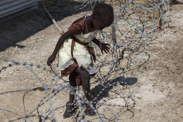 A young girl climbs through barbed wire surrounding the Dolieb Hill Presbyterian Church after service in the Protection of Civilians (POC) site at the United Nations Mission in South Sudan (UNMISS) compound in Malakal, South Sudan on Sunday, July 10, 2016. (Photo by Jane Hahn/The Washington Post)