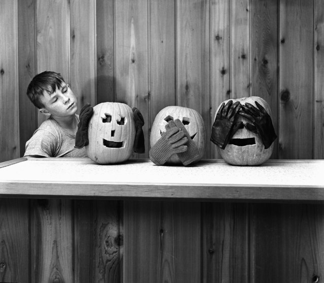 These jack-o-lanterns offer Dickie Clark, 13, of St. Paul a stern warning to mind his manners on Halloween, October 29, 1965. (Photo by AP Photo)