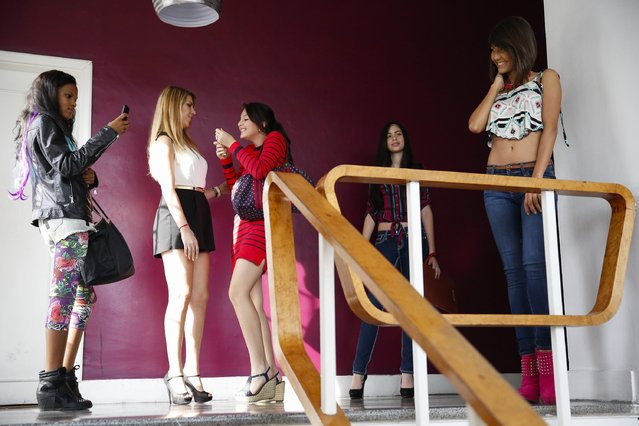 Girls take pictures and chat before class at a modelling academy in Caracas September 20, 2014. (Photo by Carlos Garcia Rawlins/Reuters)