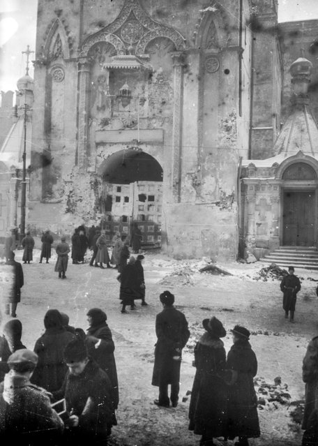 In this photo taken in October 1917, provided by Russian State Documentary Film and Photo Archive, people walk at the damaged Nikolskaya Tower right after the revolution fighting in Moscow, Russia. The 1917 Bolshevik Revolution was long before the digital revolution allowed anyone to instantly document events. But the clumsy cameras of the time still caught some images that capture the period's drama. (Photo by Russian State Documentary Film and Photo Archive via AP Photo)