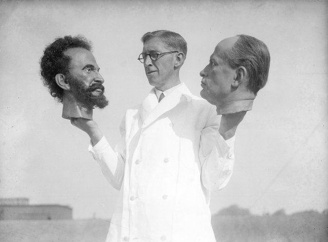 Bernard Tussaud, grandson of Swiss modeller Madame Tussaud, holds two wax heads, one of Haile Selassie, Emperor of Abyssinia (Ethiopia) and the other of Italian dictator Benito Mussolini. September 1935. (Photo by Fox Photos)