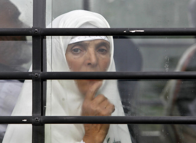 A Kashmiri Hajj pilgrim looks from a bus window, before her departure for Mecca, in Srinagar August 27, 2014. (Photo by Danish Ismail/Reuters)
