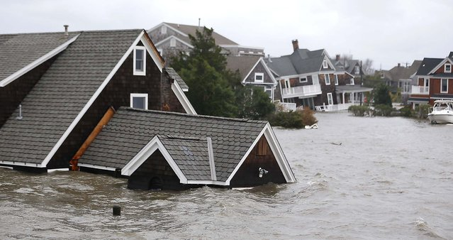 Floodwaters surround homes near the Mantoloking Bridge in Mantoloking, N.J. (Photo by Julio Cortez/Associated Press)