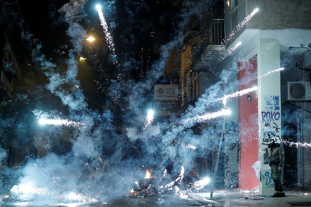 A firework explodes next to a riot policeman during clashes following a rally marking the 44th anniversary of a 1973 student uprising against the military dictatorship that was ruling Greece, in Athens, Greece on November 17, 2017. (Photo by Alkis Konstantinidis/Reuters)