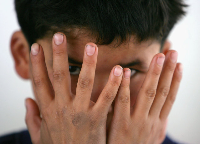 Maimaiti Aili, a 13-year old boy from China's Xinjiang Uygur Autonomous Region, covers his face with his hands at an assistance center February 24, 2005 in Shenzhen, Guangdong Province, China. (Photo by Cancan Chu/Getty Images)