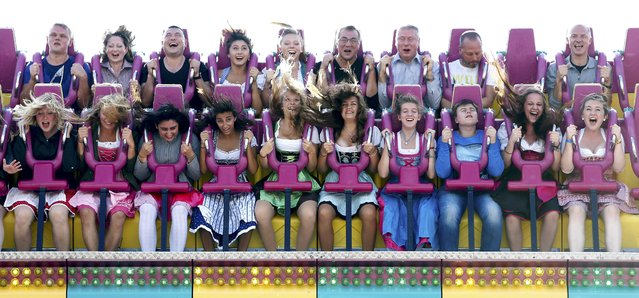 """Visitors enjoy a """"Topspin"""" fun ride during the opening day of the 182nd Oktoberfest in Munich September 19, 2015. (Photo by Michaela Rehle/Reuters)"""