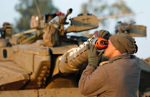 An Israeli soldier adjusts the barrel of a tank at a staging area near the border with central Gaza November 20, 2012. (Photo by Darren Whiteside/Reuters)