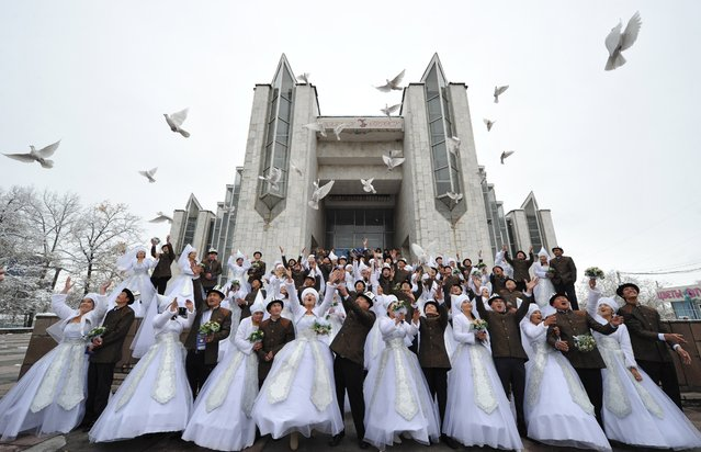 Kyrgyz couples take part in a mass wedding ceremony in the capital Bishkek on November 13, 2012. Thirty-five couples took part in the mass wedding sponsored by a state company. (Photo by Vyacheslav Oseledko/AFP Photo)