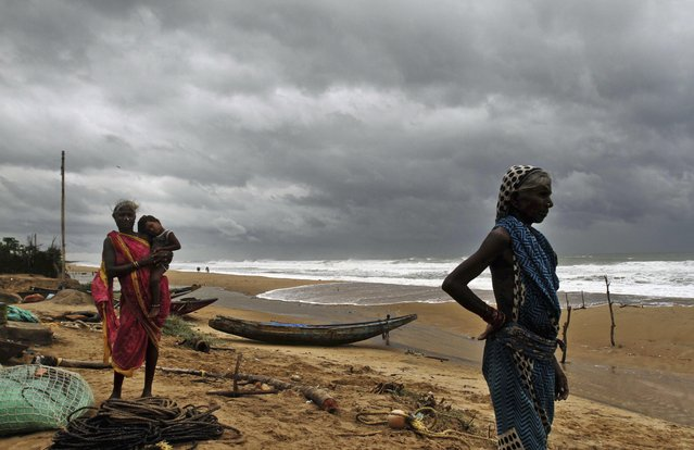 Fisherwomen watch the sea waves before evacuating the place near Podampeta village, on the outskirts of Gopalpur beach in Ganjam district, 140 kilometers (87 miles) south of Bhubaneswar, India, Saturday, October 11, 2014. (Photo by Biswaranjan Rout/AP Photo)