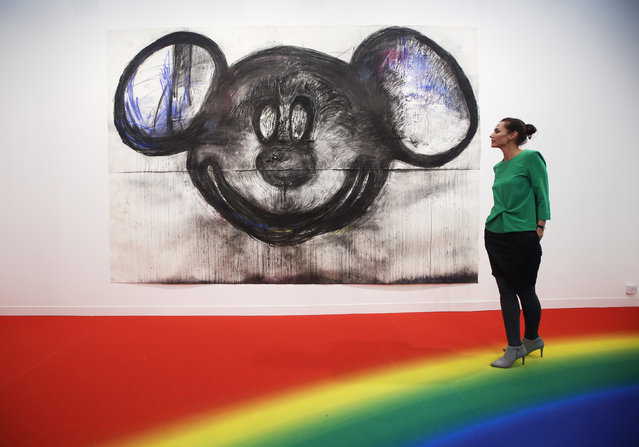 "A visitor poses with artist Joyce Pensato's artwork ""Mickey for Micky"" at the Frieze Art Fair in London, October 14, 2014. (Photo by Luke MacGregor/Reuters)"