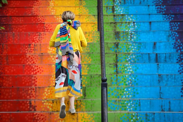 A woman walks up a stairway painted in the rainbow colors in Bucharest, Romania, Saturday, July 11, 2020. Romania reported 698 new COVID-19 infections in the last 24 hours, the highest level since the pandemic reached the country in February. (Photo by Vadim Ghirda/AP Photo)