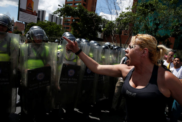 An opposition supporter shouts in front of a line of riot police while taking part in a rally to demand a referendum to remove Venezuela's President Nicolas Maduro in Caracas, Venezuela, September 1, 2016. (Photo by Carlos Garcia Rawlins/Reuters)