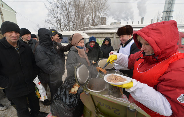 Homeless people queue to get free hot food organized by social services during frost winter day in Kiev on December 18, 2012. Nineteen people died of exposure in Ukraine in the last 24 hours amid temperatures of minus 20 degrees Celsius (minus 4 degrees Fahrenheit), bringing the toll this month to 37, the health ministry said Tuesday. (Photo by Sergei Supinsky/AFP Photo)