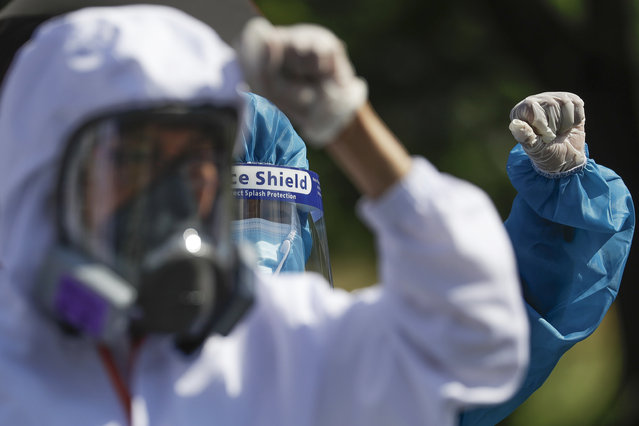 Health workers in protective suits clench fists during a protest against the State of the Nation Address (SONA) by Philippine President Rodrigo Duterte on Monday, July 27, 2020 in Metro Manila, Philippines. Hundreds of protesters marched, staged motorcades and held a rally against a new anti-terror law and other issues Monday in the Philippine capital despite police threats of arrests ahead of the president's annual state of the nation speech. (Photo by Aaron Favila/AP Photo)