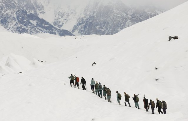 A group of Pakistani soldiers carry their guns uphill along the K2 base camp trek in the Karakoram mountain range in Pakistan September 8, 2014. A local porter receives 700 Pakistani Rupee ($6.8) per day and usually carries 55 pounds. Owners of mules can earn three times as much, as their animals carry 165 pounds. (Photo by Wolfgang Rattay/Reuters)