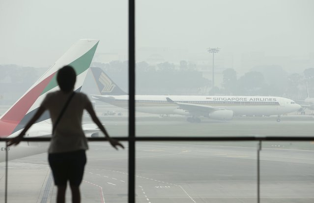 A woman watches as a Singapore Airlines plane prepares to take off, from a viewing gallery in Singapore's Changi Airport September 29, 2015. (Photo by Edgar Su/Reuters)