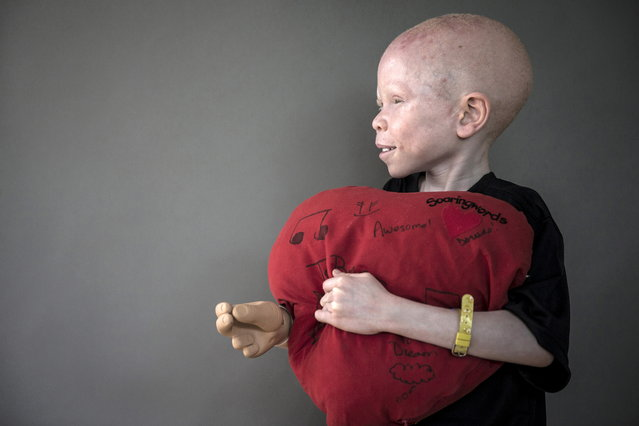 5-year-old Baraka Cosmas from Tanzania poses for a portrait with a plush heart that he says makes him feel safe at night and that he sleeps with. (Photo by Carlo Allegri/Reuters)