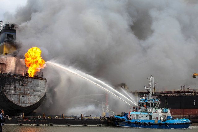 Fire fighters onboard a vessel try to extinguish a fire on a tanker ship docked in Belawan, Indonesia on May 11, 2020. (Photo by Ivan Damanik/AFP Photo)