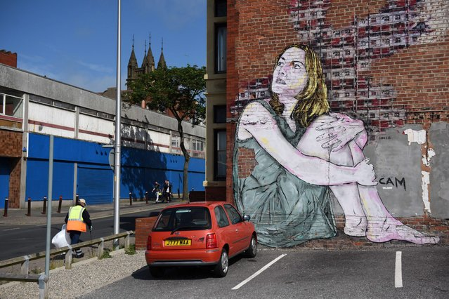 "A workman walks past a large mural on the side of a building during the ""Sand Sea & Spray"" Urban Art Festival in Blackpool, north west England on July 11, 2015. (Photo by Oli Scarff/AFP Photo)"