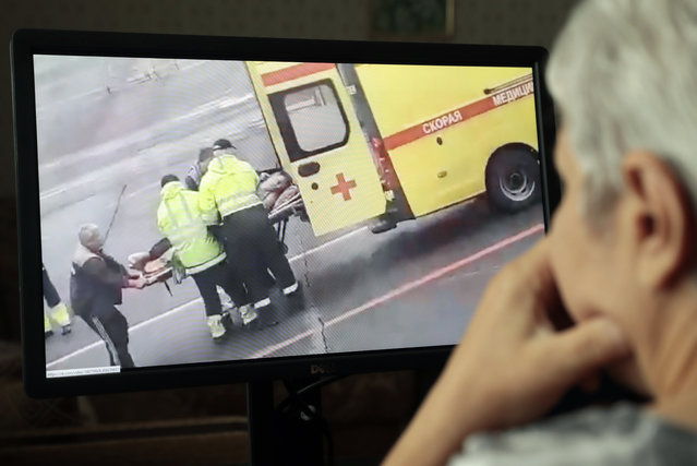 A person (R) in Moscow watches a video on social media showing Russian opposition activist and anti-corruption fund head Alexei Navalny being carried on a stretcher by an ambulance team, in Omsk, Russia, 20 August 2020. Navalny's spokeswoman Kira Yarmysh said on social media on 20 August that the opposition leader and critic of President Vladimir Putin was taken to hospital for alleged poisoning after he started feeling unwell during a flight from Siberia to Moscow. The plane made an emergency landing in the city of Omsk. (Photo by Sergei Chirikov/EPA/EFE)