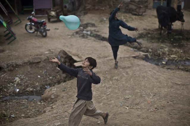 An Afghan refugee boy chases a balloon while playing in a poor neighborhood on the outskirts of Islamabad, Pakistan, Sunday, February 2, 2014. (Photo by Muhammed Muheisen/AP Photo)