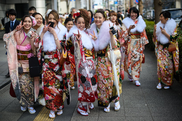 Women wearing kimonos gesture at the camera as they leave after attending a Coming of Age ceremony on January 8, 2018 in Yokohama, Japan. (Photo by Carl Court/Getty Images)